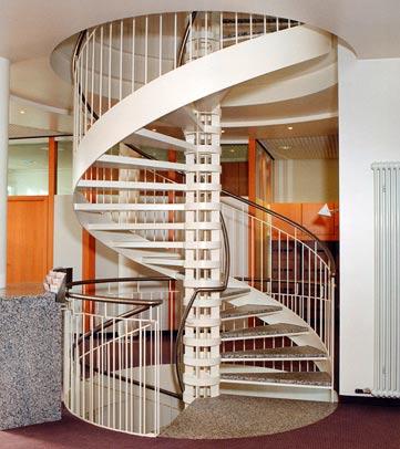 Weiße Stahlspindeltreppe mit einer geschweißten Spindel und einer Außenwange zur Aussteifung der Treppe. Die Stahlspindel wurde aus einzelnen Segmenten zusammengeschweißt.