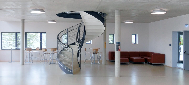 Wendeltreppe aus Stahl oder Stahlwendeltreppe mit einem besonderem X-TEND Edelstahlnetze als Geländerfüllung. Die geschwungene Treppenform ist einzigartig im sonst rechteckigem Gebäude.